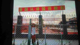 幼稚園の周囲の壁には有刺鉄線が張り巡らされている。壁に掲げられているのは「愛国心は中国語を話すことから始まる」というスローガンだ。