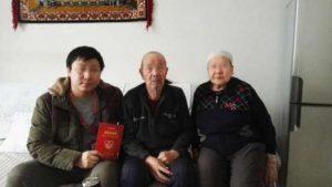 漢族の職員とウイグル族のホームステイ家族の写真。「ホームステイカード」に署名した後に撮影。(インターネットから)