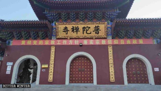 普陀禅寺の前には「信教の自由の政策を実行せよ」と書かれた、中国共産党による皮肉めいたプロパガンダのスローガンが掲示されている。