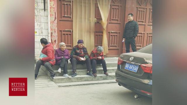 封鎖された教会の扉の前で祈り、涙を流す高齢の信者。
