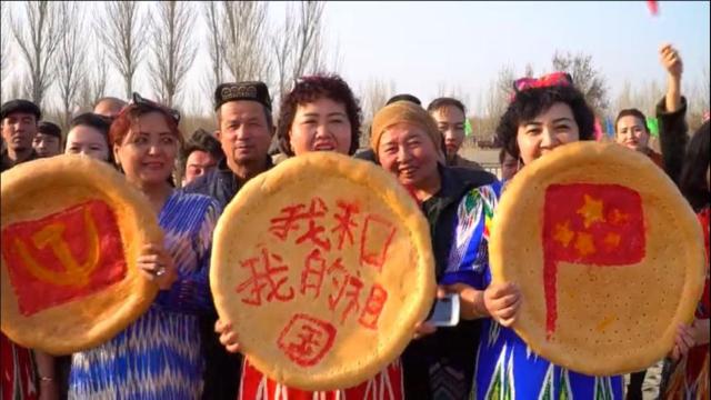 新疆のトルファンで行われた春の祝祭で撮影されたウイグル族のナンの写真 - ハンマーと鎌の中国共産党のロゴ、「私と私の国」を意味するスローガン、中国の国旗(左か右の順番)があしらわれている。