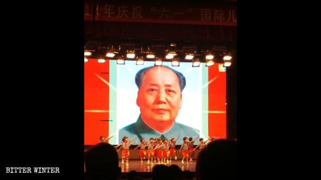 毛沢東の肖像画が掲げられた舞台で「紅い」公演を行う子どもたち。
