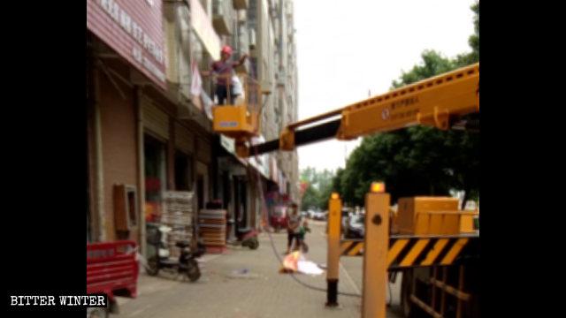 武漢市江夏区で、看板を強制撤去する都市管理当局。