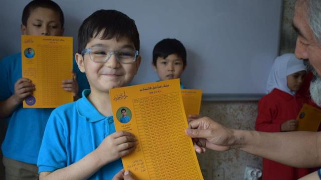 ラマダンのカレンダーを受け取るヒラーイさんの学校の生徒たち。
