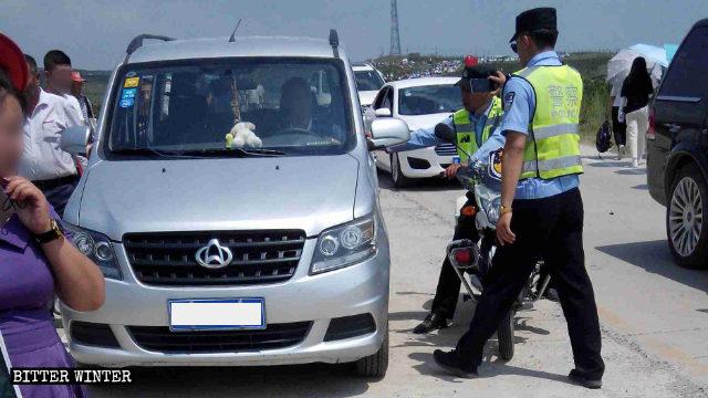 磨子山の巡礼地の道中で車を止めさせる警察。
