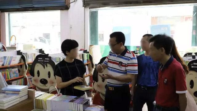 広東省の書店に並ぶ出版物を点検する政府当局。