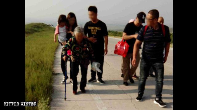 白髪の高齢女性は山頂の巡礼地まで杖に頼って行かねばならなかった。