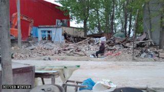 駐馬店市で、取り壊された自宅のがれきのそばに腰かける年配の女性。