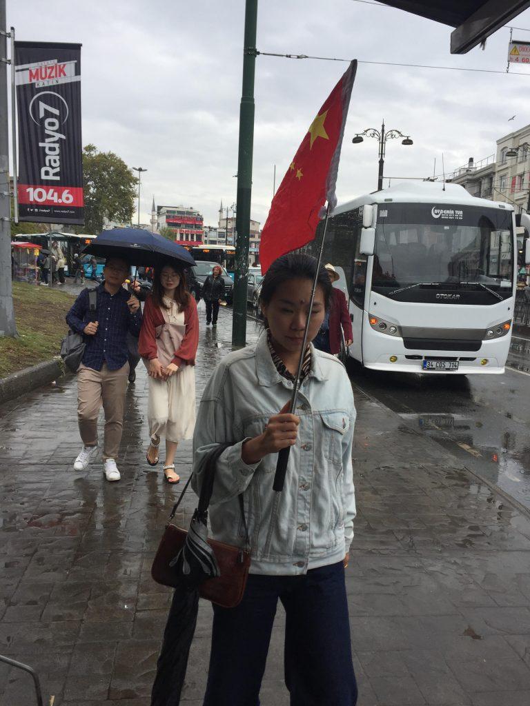 イスタンブールの通りで高く掲げられる中国の紅旗。ツアーガイドが訪問者を古代のバザールに案内している。