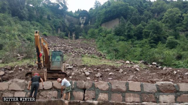 仏像を覆う準備として建設作業員が保持壁を組んでいる。