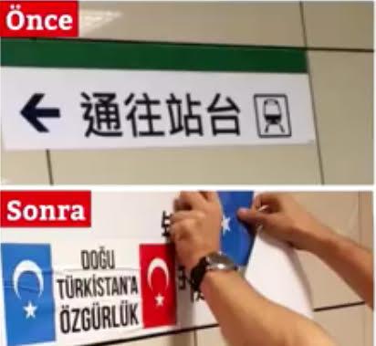 ウイグル族の共鳴者のあるトルコ人が、路面電車のプラットフォームを示す中国語の案内板の下に東トルキスタンとトルコの国旗を貼っている。