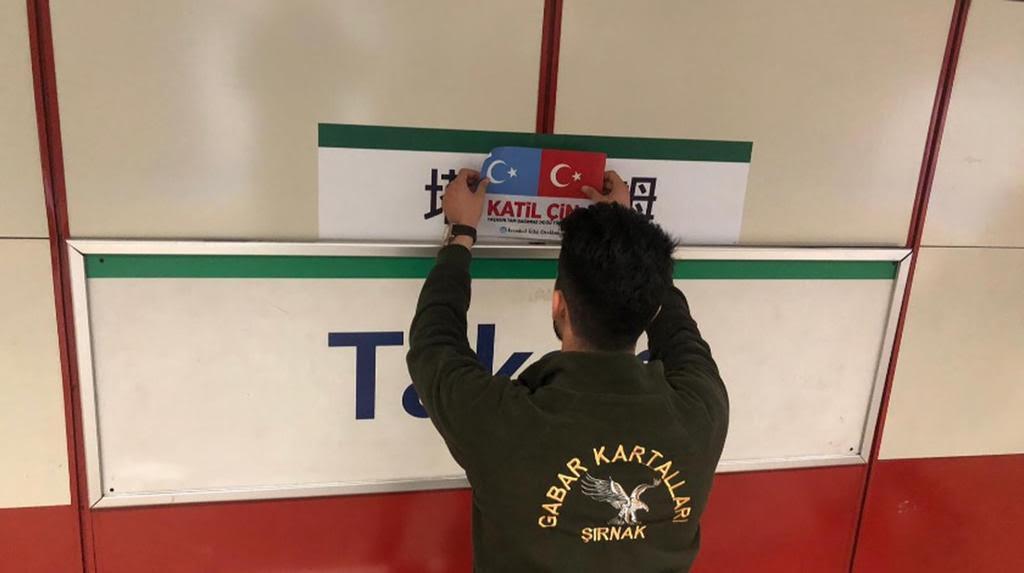 ウイグル族に共鳴するのあるトルコ人が、タクシムにある路面電車の駅に貼られた中国語の標識を東トルキスタンとトルコの国旗と「殺人者中国」を意味する「カティル・チン(katil çin)」というトルコ語の言葉で覆っている。