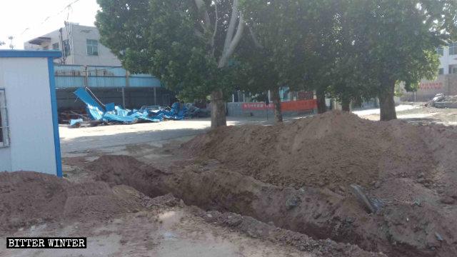 ショベルカーが任荘村の教会の前に大きな穴を掘った。